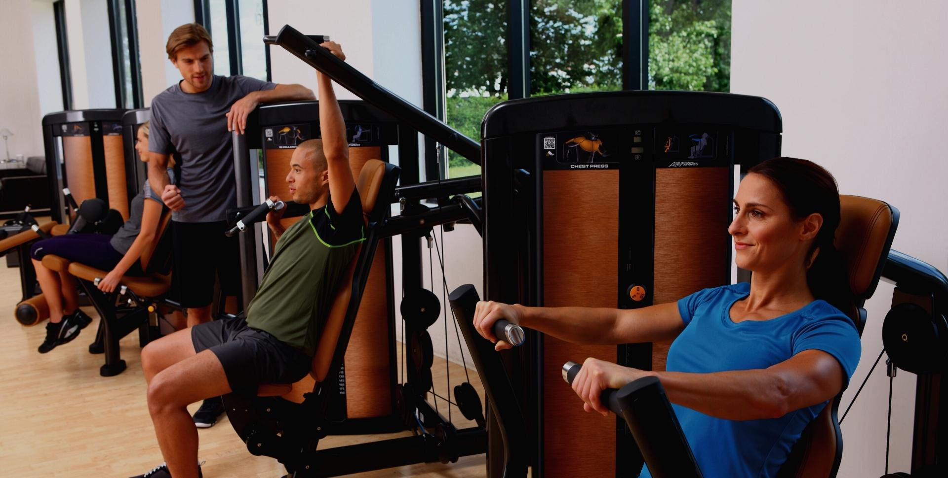 People working out at gym using strength machines in fitness 19 midland park new jersey gym